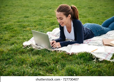 Portrait of a smiling beautiful student girl doing homework on laptop computer while lying on the grass at park