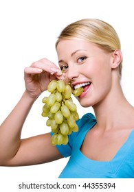Portrait of  smiling Beautiful woman bits grapes - over white background