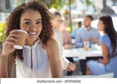 Portrait of smiling beautiful woman having coffee in restaurant