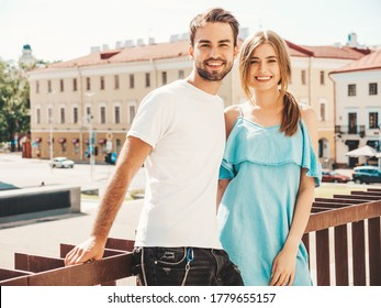 Portrait of smiling beautiful woman and her handsome boyfriend.Woman in casual summer jeans dress.Happy cheerful family.Female having fun.Couple posing on the street background
