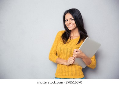 Portrait of a smiling beautiful woman holding laptop over gray background and looking at camera