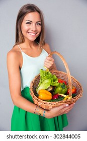 Portrait of a smiling beautiful woman holding basket with vegetables on gray background