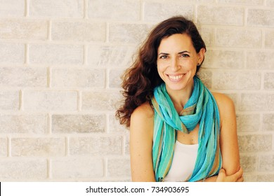 Portrait of smiling beautiful woman in turquoise skirt standing against of city grey wall