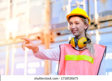 Portrait of smiling beautiful worker or technician with engineer uniform point to forward direction in the shipping container workplace area during day time with concept of good industrial business.