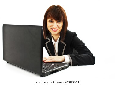 Portrait of a smiling beautiful young business woman working on laptop.  Isolated on white background.