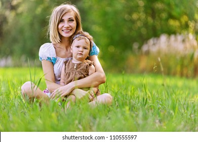 Portrait of smiling beautiful young woman and her little daughter sitting on grass, against green of summer park.
