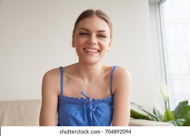 Portrait of smiling beautiful young woman sitting on sofa in living room and looking at camera. Happy lady enjoying pleasant conversation in Internet, speaking with friends via online video chat