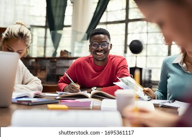 Portrait of smiling black student in library with classmates studying. Happy university student sitting in library with friends. Portrait of smiling young man looking at camera in a college library.