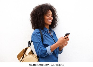 Portrait of smiling black woman with smart phone and backpack