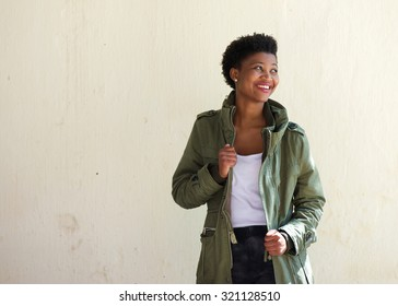 Portrait of a smiling black woman standing outside with green jacket