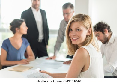 Portrait of a smiling blond assistant, she is turned back on her chair at an office business meeting. The team is sitting at a table in a luminous white open space, brainstorming some new ideas.