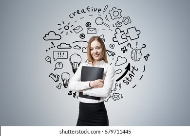 Portrait of a smiling blond businesswoman hugging her black folder and standing near a dark gray wall with a startup sketch on it.