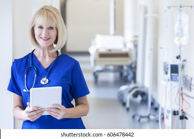 Portrait smiling blonde Caucasian female clinical hospital nurse in scrubs using wireless tablet at modern medical center
