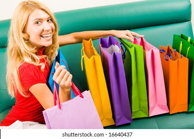 Portrait of smiling blonde sitting on sofa with several colorful  shoppingbags