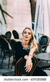 portrait of smiling blonde sitting at a table in cafe