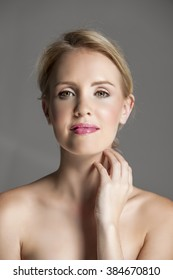 Portrait of smiling blonde woman with natural makeup and soft pink lips, touching her hand to her neck.