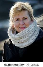 Portrait of a smiling blonde woman wearing a white scarf and black coat on a cold and sunny day