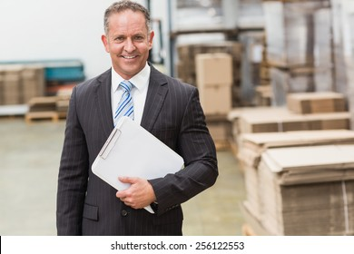 Portrait of a smiling boss holding clipboard in a large warehouse