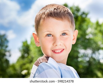 Portrait of a smiling boy with blue eyes on a background of spring landscape. Green trees, blue sky with white clouds