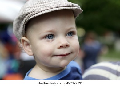 Portrait of a smiling boy in cap in summer park