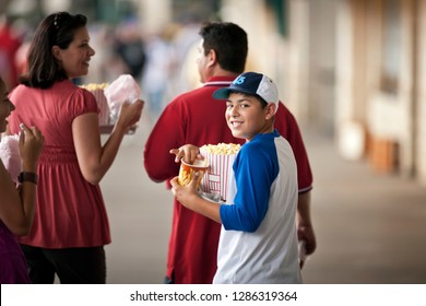 Portrait of a smiling boy carrying snacks to a baseball game with his family.