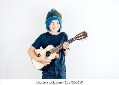 Portrait of a smiling boy in casual clothes and hat playing ukulele. Copy space on white background.