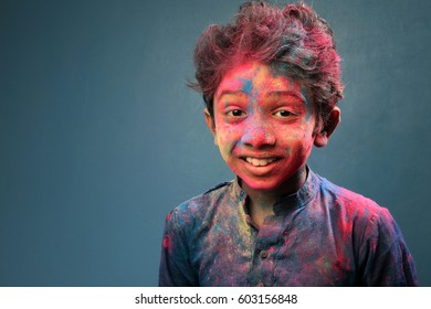 Portrait of a smiling boy with face smeared with Holi colors
