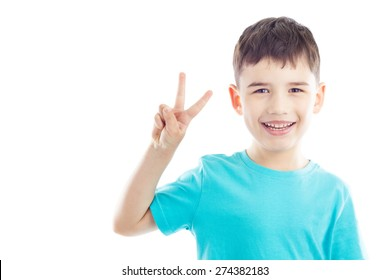 Portrait of smiling boy, he shows hand victory sign
