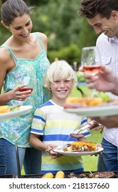 Portrait of smiling boy holding plate of barbecue