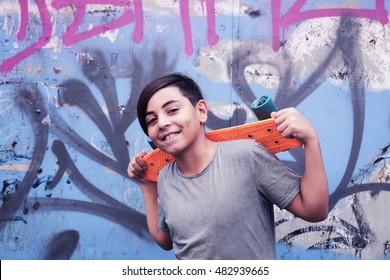 Portrait of smiling boy with skateboard standing in front of graffiti covered wall.