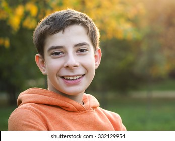 Portrait of a smiling boy. Teenager. Casual Thirteen year old teenage boy smiling outside