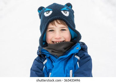 A portrait of a smiling boy in warm winter clothes on a white snow background