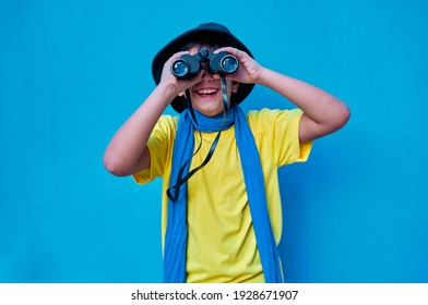 A Portrait of smiling boy in yellow t-shirt looking at camera through binoculars, on blue background. Copy space