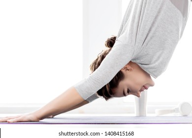 Portrait of smiling brunette female bent over to position downward facing dog. Young athletic woman in grey clothes is practicing yoga at light fitness studio. Healthy lifestyle concept.