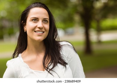Portrait of a smiling brunette standing in the park