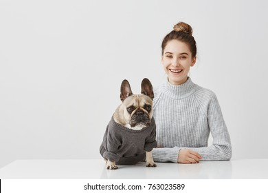 Portrait of smiling brunette woman with hair tied in topknot working at home office. Female freelancer sitting at the table in workshop in company of dog.  Friendship concept