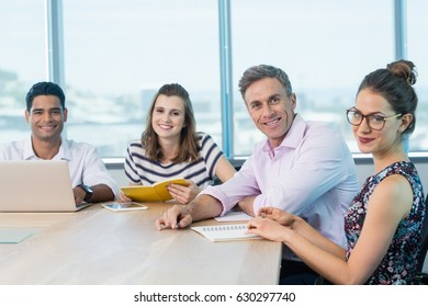 Portrait of smiling business colleagues with laptop in meeting at office