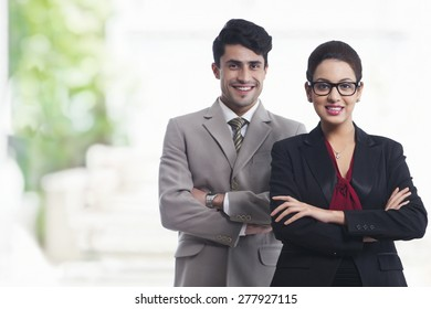 Portrait of smiling business colleagues standing arms crosses in office
