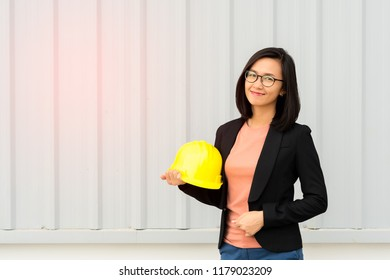 Portrait smiling business engineer woman with holding yellow safety helmet on metal sheet background, happy businesswoman looking to the camera