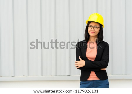 8700fe1f6b0 Portrait smiling business engineer woman with yellow safety helmet on metal  sheet background