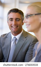 Portrait of smiling business executive with female coworker in the foreground.