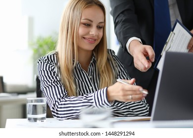 Portrait of smiling business lady discussing with partner conditions of contract. Cheerful businesswoman reading and correcting important documents. Biz concept. Blurred background