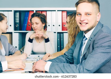 Portrait of smiling business man, with female colleagues on the background. Serious business and partnership, job offer concept.