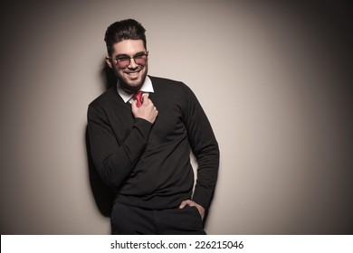 Portrait of a smiling business man leaning on a grey wall while fixing his tie. On grey background.