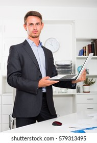 Portrait of smiling business man standing and holding computer in hands in office