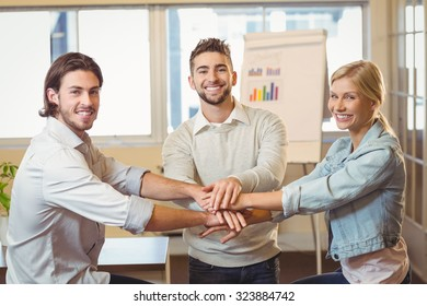 Portrait of smiling business people with hand stacked in meeting room at creative office