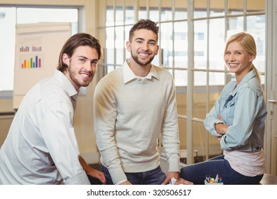Portrait of smiling business people in meeting room at creative office
