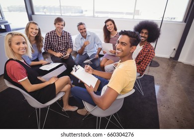 Portrait of smiling business people sitting while discussion in office