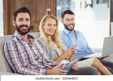 Portrait of smiling business people using technologies in office