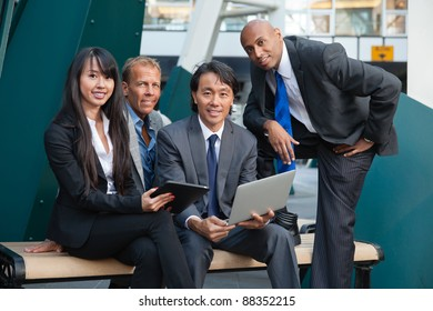 Portrait of smiling business people using electronic gadgets
